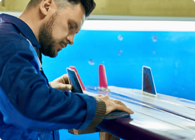 handsome-man-polishing-cistom-surfing-board-workshop