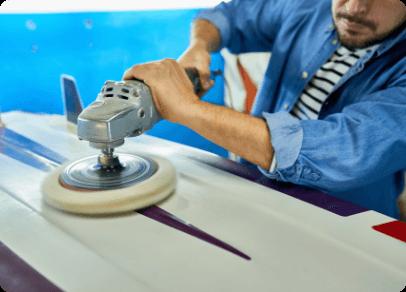 tanned-man-polishing-surfing-board-workshop